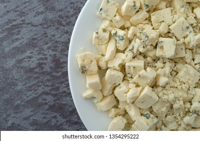 Overhead close view of a portion of crumbled blue cheese on a white plate atop a gray background illuminated with natural lighting.