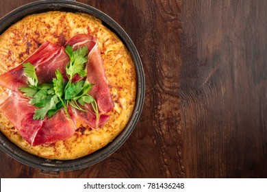 An overhead closeup photo of a Spanish tortilla in a traditional tortillera, with jamon and parsley, on dark rustic textures with a place for text