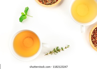 An overhead closeup photo of tea, two cups and two bowls with loose tea leaves, on a white background with a thyme branch. mint leaves and copy space
