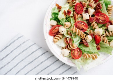 Overhead, close-up shot of BLT pasta salad with crispy bacon, grape tomatoes, green leafy lettuce and fresh mozzarella in white bowl with blue striped linen.