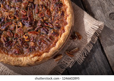 Overhead closeup view of a whole pecan pie on a rustic wooden surface