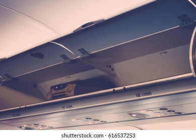 Overhead compartment in commercial airplane ( Filtered image processed vintage effect. )