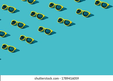 Overhead composition of many vivid color plastic sunglasses on turquoise blue background with copy space. Minimalist photo pattern of stylish yellow sunglasses with harsh shadow as summer concept.