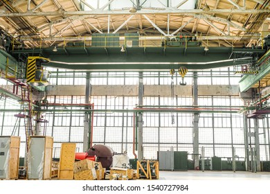 Overhead crane in engineering plant shop. Industrial metalwork production hall and warehousing workshop. Reinforced concrete industrial long-span building.