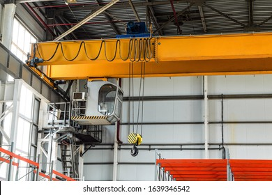 Overhead crane with hook in engineering plant shop. Cabin of crane operator with jib crab trolley. Landing staircase.