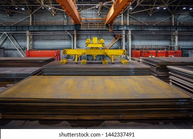Overhead crane with magnetic grippers lifting steel sheets.