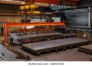 Overhead crane with vacuum handling grippers lifting iron sheets.