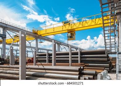 overhead cranes over railroad in metal pipe outdoor warehouse