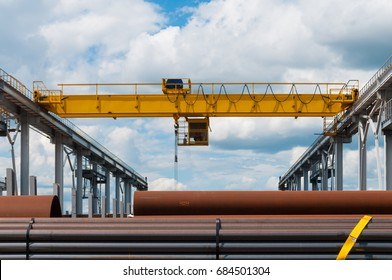 overhead cranes over railroad in metal pipe outdoor warehouse