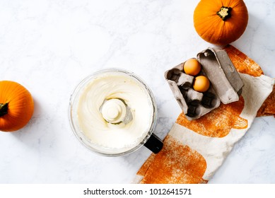 Overhead of cream cheese mixture with spices in food processor with pureed pumpkin for cheesecake bars on white marble surface with whole pumpkins.