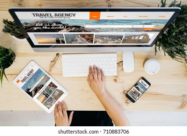overhead desktop with travel agency website on devices screen. Some elements furnished by nasa.