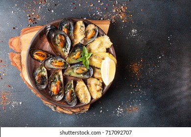 Overhead of dinner table. Assorted delicious grilled barbecue meat and seafood. Pork teaks, trout, mussels, shrimps, dried tomato, cherry tomato, chili pepper, glasses of wine.Bbq party concept.