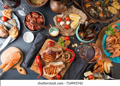 Overhead of dinner table. Barbecue meat and seafood with vegetable. Pork grilled steaks, grilled salmon trout, mussels, shrimps, dried tomato, cherry tomato,  glass of  wine. Picnic bbq party concept.
