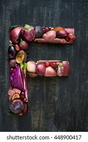 overhead display of purple fruit and vegetables arranged in alphabet letter shapes.