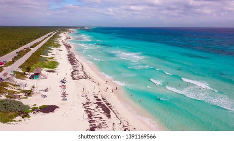 Overhead drone shot of swimmers on a tropical beach in Cozumel, Mexico.