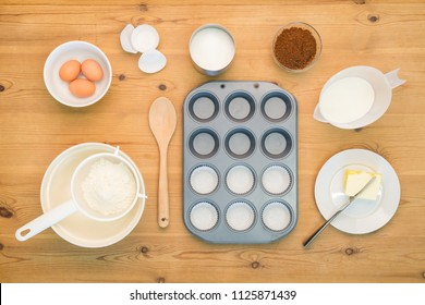 Overhead flat lay arrangement of Cup Cake making ingredients and equipment on a kitchen table.