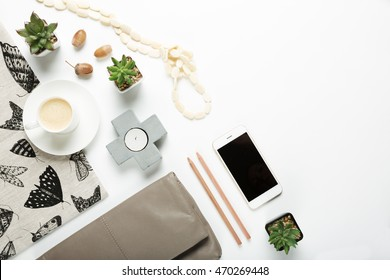Overhead flat lay collection of desktop fashion and home items with negative space