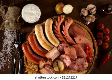 Overhead of grilled and boiled meat sausages with vegetables and white sauce on a dark  kitchen table