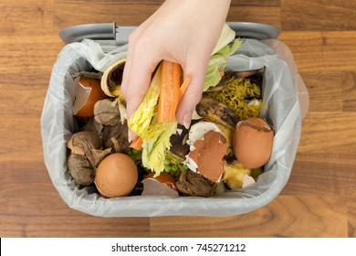 Overhead of a hand placing food scraps into a garbage bin