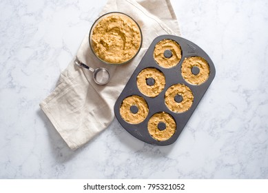 Overhead of homemade apple donut batter in a donut pan with silver measuring cup and beige linen.