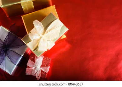 An overhead, horizontal shot of Christmas gift boxes, wrapped and tied with ribbon bows.  Copy space provided to the right on a reflective red background.
