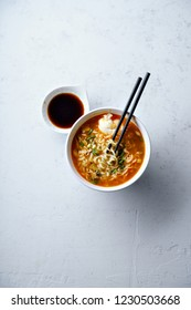 Overhead image of easy japanese ramen with noodles, pork broth, egg and leek in white bowl on concrete background