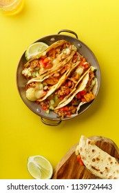 Overhead image of mexican tacos with chili con carnes and grated cheese served over a yellow background