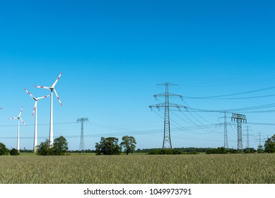 Overhead lines and wind turbines on a sunny day seen in Germany