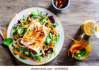 Overhead of marinated tofu salad with spicy peanut vinaigrette, sliced jalapenos, carrots, red onion, almonds and salt and pepper with pretty wooden salad fork.