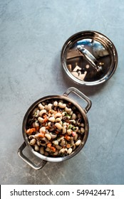 Overhead of mini copper pot of Southern black eyed pea salad with fresh herbs, carrots and red onion tossed in oil on metal surface with brown leather seat in the background.