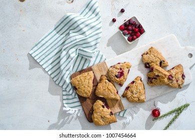 Overhead of mini cranberry whole wheat scones and whole cranberries on white marble board with green and white striped linen.
