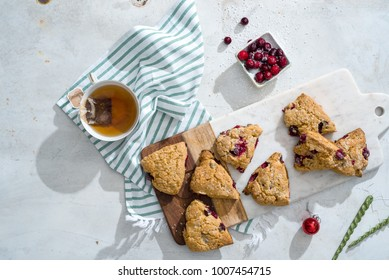 Overhead of mini cranberry whole wheat scones and whole cranberries on white marble board with a mug of hot tea.