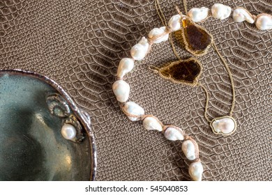 Overhead of natural gemstone topaz gold earrings with freshwater pearl necklaces on brown crocodile surface with blue ceramic bowl.