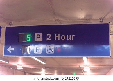 Overhead neon sign at indoor  airport parking lot displays number of available parking spaces. Available empty spots display counter information. 2 hour parking limitation