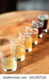 Overhead on a flight of craft beers in pint glasses, with ascending volumes arranged in diagonal row, at a local brewery
