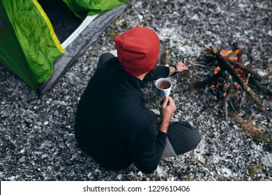 Overhead outdoor shot of young male drinking hot beverage in mountains near to bonfire. Rear view of traveler man in red hat, sitting near to camping tent, holding a mug of tea after hiking. Travel