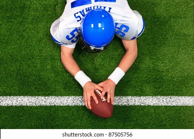 Overhead photo of an American football player making a touchdown with both hands on the ball. The uniform he's wearing is one I had made using my name and does not represent any actual team colours.