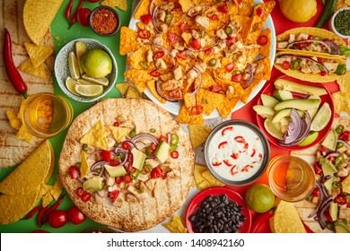 An overhead photo of an assortment of many different Mexican foods, including tacos, guacamole, nachos with grilled chicken, tortillas, salsas and others