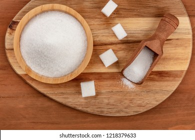 An overhead photo of a bowl and a scoop of white sugar, with sugar cubes, shot from the top on dark rustic wooden backgrounds with copy space