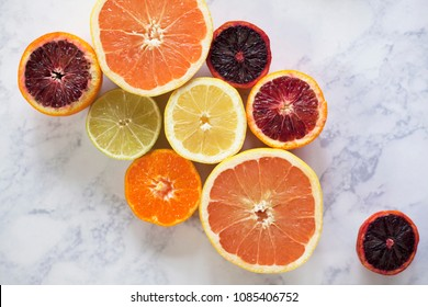 Overhead photo of citrus fruit spread on white marble countertop