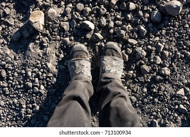 Overhead photo of feet on a background of brown soil . Man feet