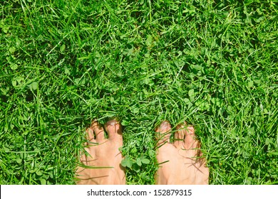 Overhead photo of feet on grass background. Close up of feets on the grass.