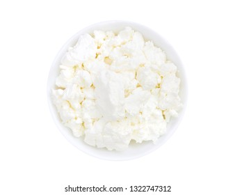 An overhead photo of fresh natural cottage cheese in a white ceramic bowl isolated on white. Organic eco healthy meal, dairy product. Top view