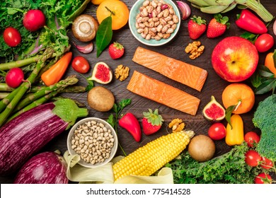 An overhead photo of fresh vegetables, fruits, legumes, and fish, healthy diet ingredients, shot from above on a dark rustic texture. Organic food or groceries shop banner