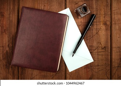 An overhead photo of a leather bound journal, a blue envelope, an ink well and pen, shot from above on a dark rustic background with a place for text