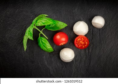 An overhead photo of Mozzarella cheese balls with fresh basil leaves and cherry tomatoes, the ingredients of the Italian Caprese salad, on a black background with a place for text