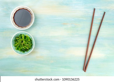 An overhead photo of a pair of chopsticks with a bowl of soy sauce and wakame seaweed salad on a teal background with copy space