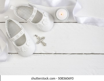 Overhead photo of pair of white baby shoes, candle and Christian cross pendant on white wood table