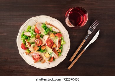 An overhead photo of a plate of chicken Caesar salad with cherry tomatoes, Parmesan cheese, and croutons on a dark rustic background texture with a glass of wine, a fork, a knife, and copy space