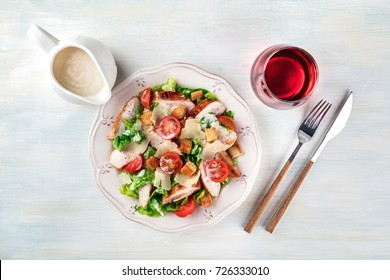 An overhead photo of a plate of chicken Caesar salad on a light background with a gravy boat, a fork and a knife, a glass of wine, and a place for text